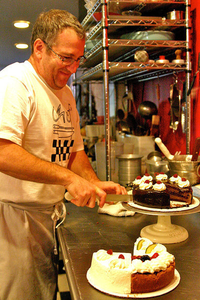 Tom Hambor, the pastry chef, slices some of his delicious creation. (credit: Hannah Rosen | Photo Staff)