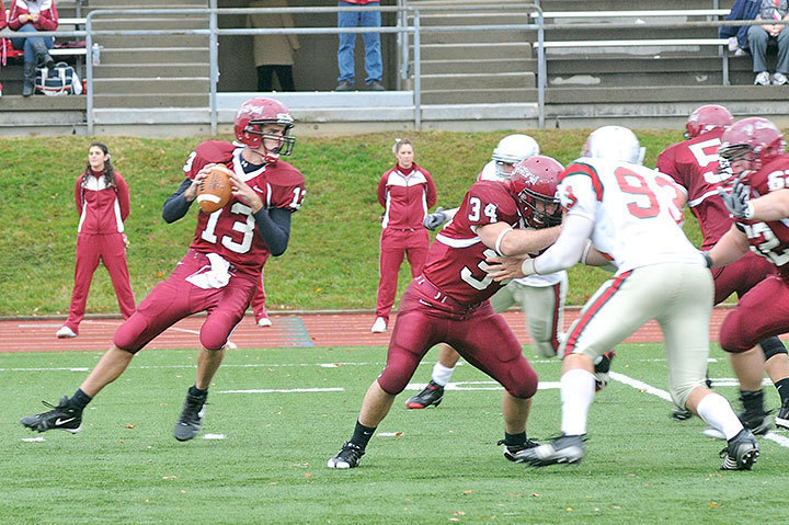 Senior quarterback Phil Pantalone looks for an opening against Washington University, while junior Justin Pratt blocks a rushing Bear player. The Tartans defeated the Bears 21–13.