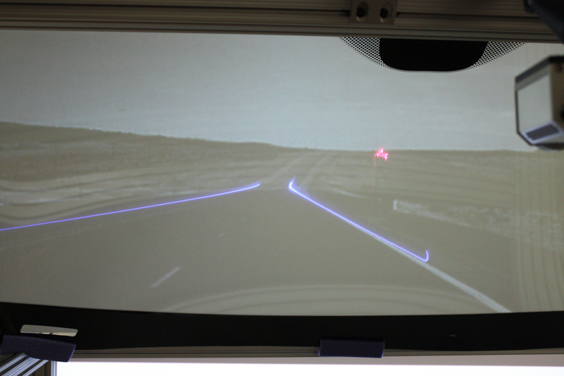 "A new windshield, developed by GM and researchers at Carnegie Mellon and the University of Southern California, uses ultraviolet lasers to ""see"" roads and street signs through fog. The windshield has phosphors that can light up and display the contours of the road. (credit: Courtesy of GM)"