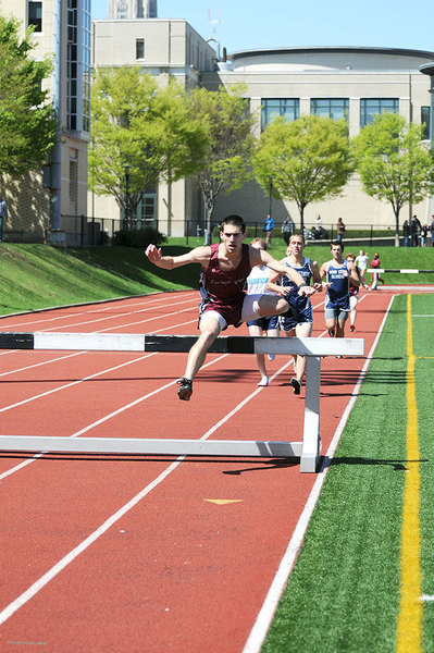 Senior Chris Rizzo jumps over a hurdle in Gesling Stadium during the 3000-meter steeplechase. Rizzo took first place with a time of  10:04.68. (credit: Thomas Hofman/Photo Staff )