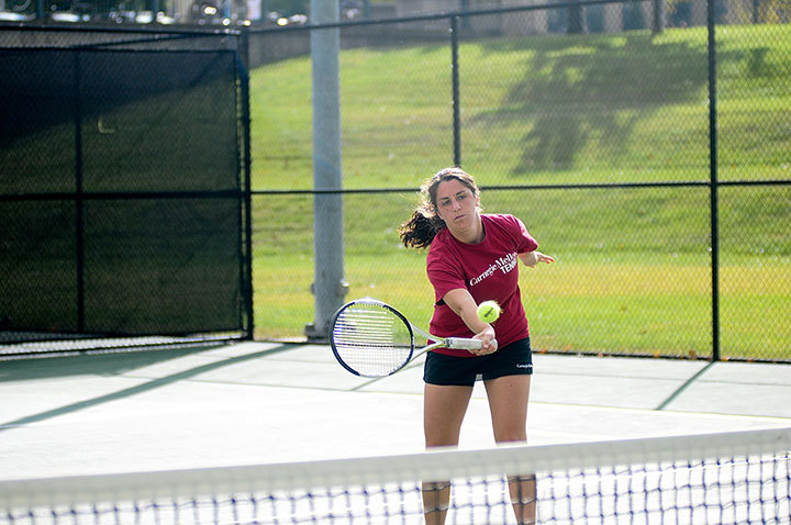 Senior Danielle Rosenfeld charges the net and hits a forehand volley. Rosenfeld won both of her singles matches 8–0. (credit: Yihuan Zhou/Photo Staff)