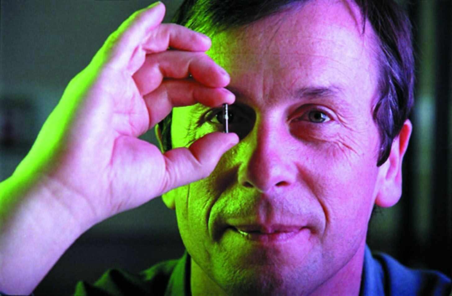 Kevin Warwick poses with a transponder that can be implanted in a human. Warwick already has a similar chip in his arm that allows him to control various appliances in his office, making him the world's first cyborg. (credit: Courtesy of Kevin Warwick)