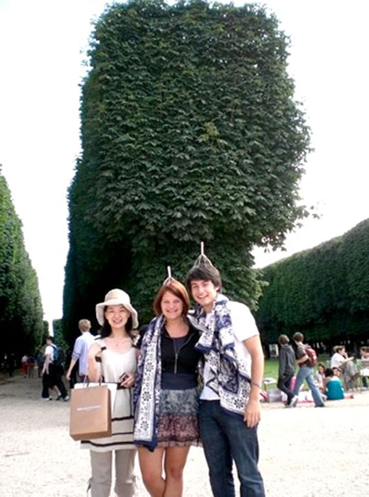 At the Jardin Luxembourg, after illegally frolicking on the grass while wearing scalp massagers as hats, Kelly and senior Science and Humanities Scholar Cristian Young took a photo with a Japanese tourist. (credit: Courtesy of Kelly Stewart)