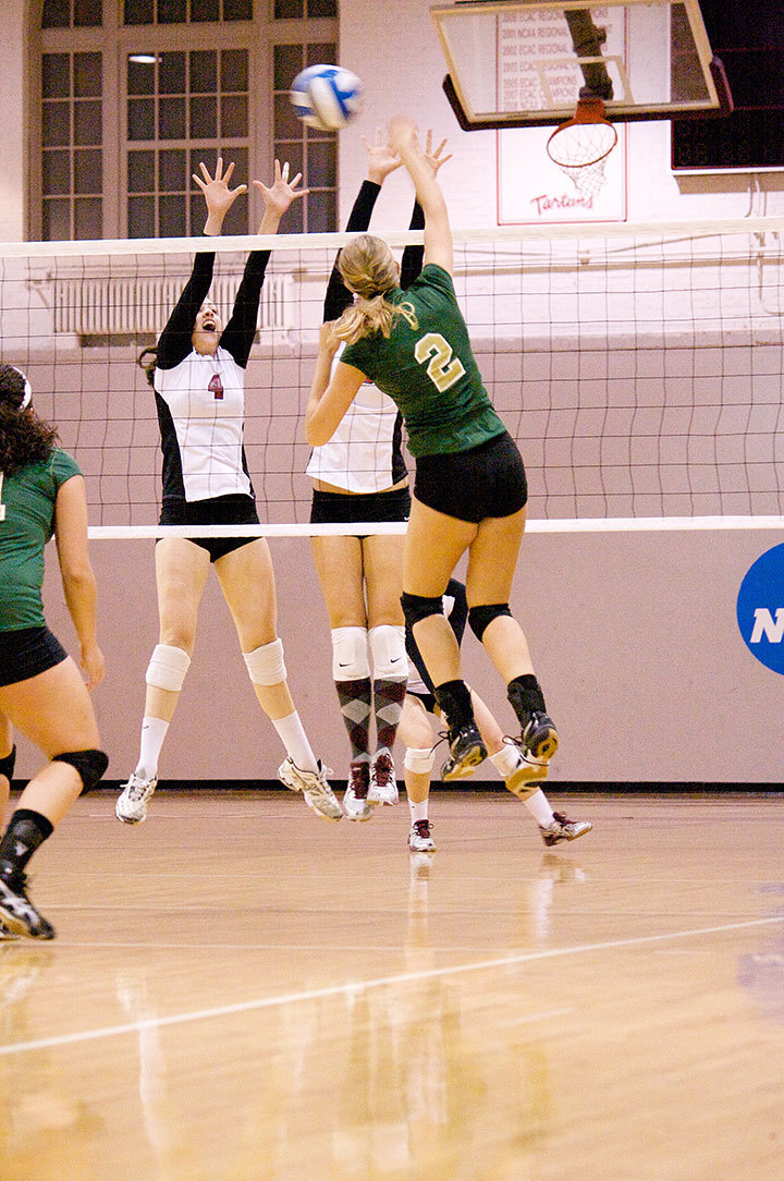 First-year Olivia Mora (No. 4) reaches up to block a kill attempt. (credit: Jonathan Carreon/Photo Staff )