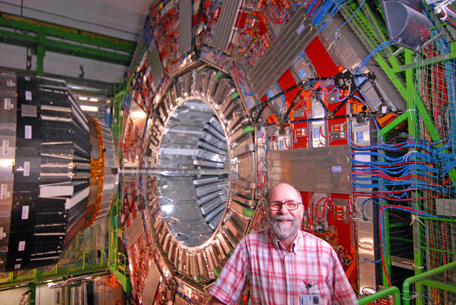 Thomas Ferguson, a professor at Carnegie Mellon, poses with the Compact Muon Solenoid at the Large Hadron Collider in Geneva, which works to detect subatomic particles such as the elusive Higgs boson particle. The Higgs boson particle is the only predicted particle in the Standard Model that has not yet been discovered. (credit: Courtesy of Thomas Ferguson)