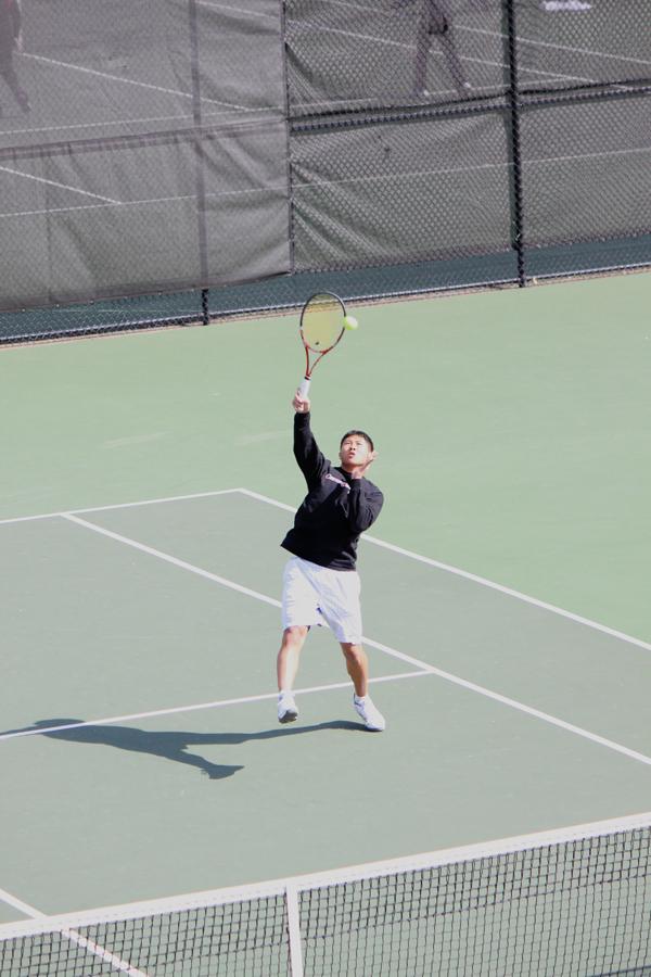 Sophomore Jooho Yu hits an overhead during a doubles match against Walsh University. (credit: Alexandre Kaspar/Photo Staff)