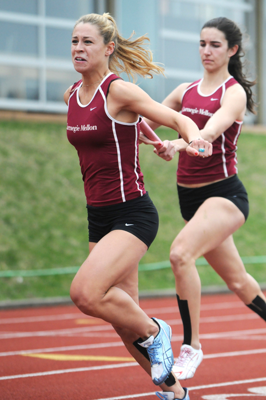 Jackie Guevel (right) hands the baton off to Kimberley Nederhof during a meet. Guevel set school and UAA records in two events last weekend. (credit: File Photo)