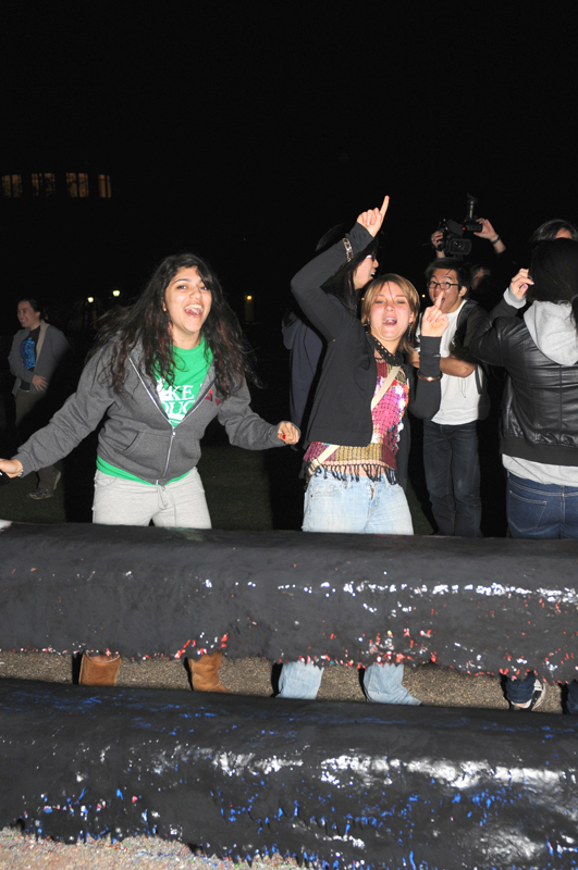 Students gather together at midnight to paint the Fence, which serves as a community message board. (credit: File Photo)
