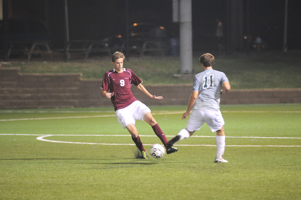 Forward Max Tassano dribbles around St. Vincent's midfielder Daniel Moore in the second game of the CMU Invitational. Tassano scored one goal in the game, his first of the season. (credit: Celia Ludwinski/Operations Manager)