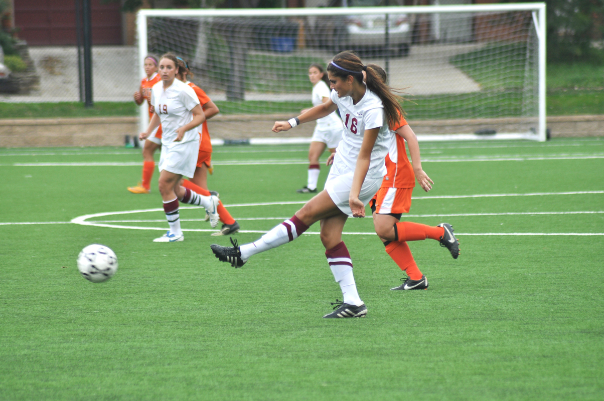 Junior defender Mitra Ebrahimi sends a pass across the field as first year forward Courtney Brant watches. (credit: Alan Vangpat/Layout Staff)