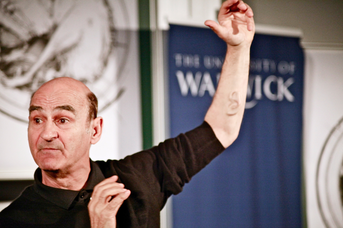 Performance artist Stelarc shows his left-arm ear implant during a keynote talk at the University of Warwick last June. (credit: Courtesy of Andy Miah via Flickr)