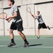 Junior Duke Miller hits a backhand during a doubles match while first-year Will Duncan is ready at the net.