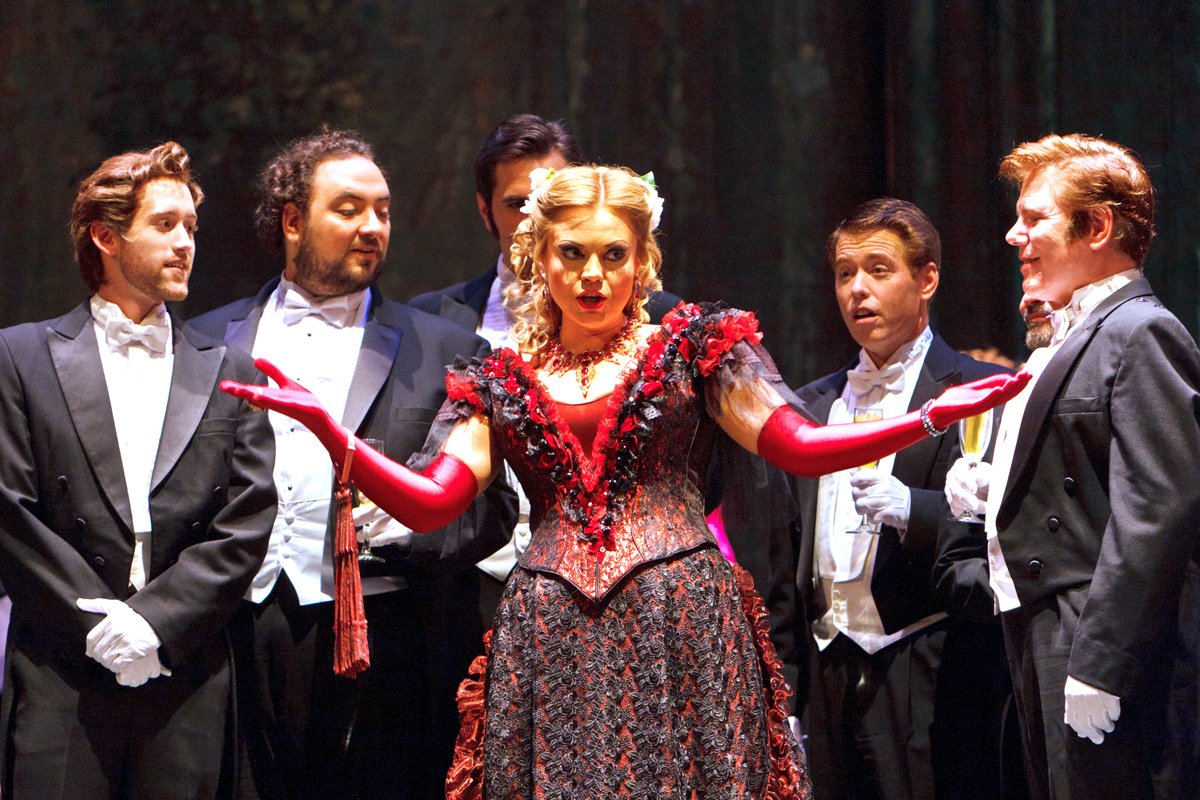 Violetta, played by Anna Sumuil, is surrounded by her admirers in Verdi's La Traviata. (credit: Courtesy of David Bachman)