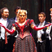 Violetta, played by Anna Sumuil, is surrounded by her admirers in Verdi's La Traviata.