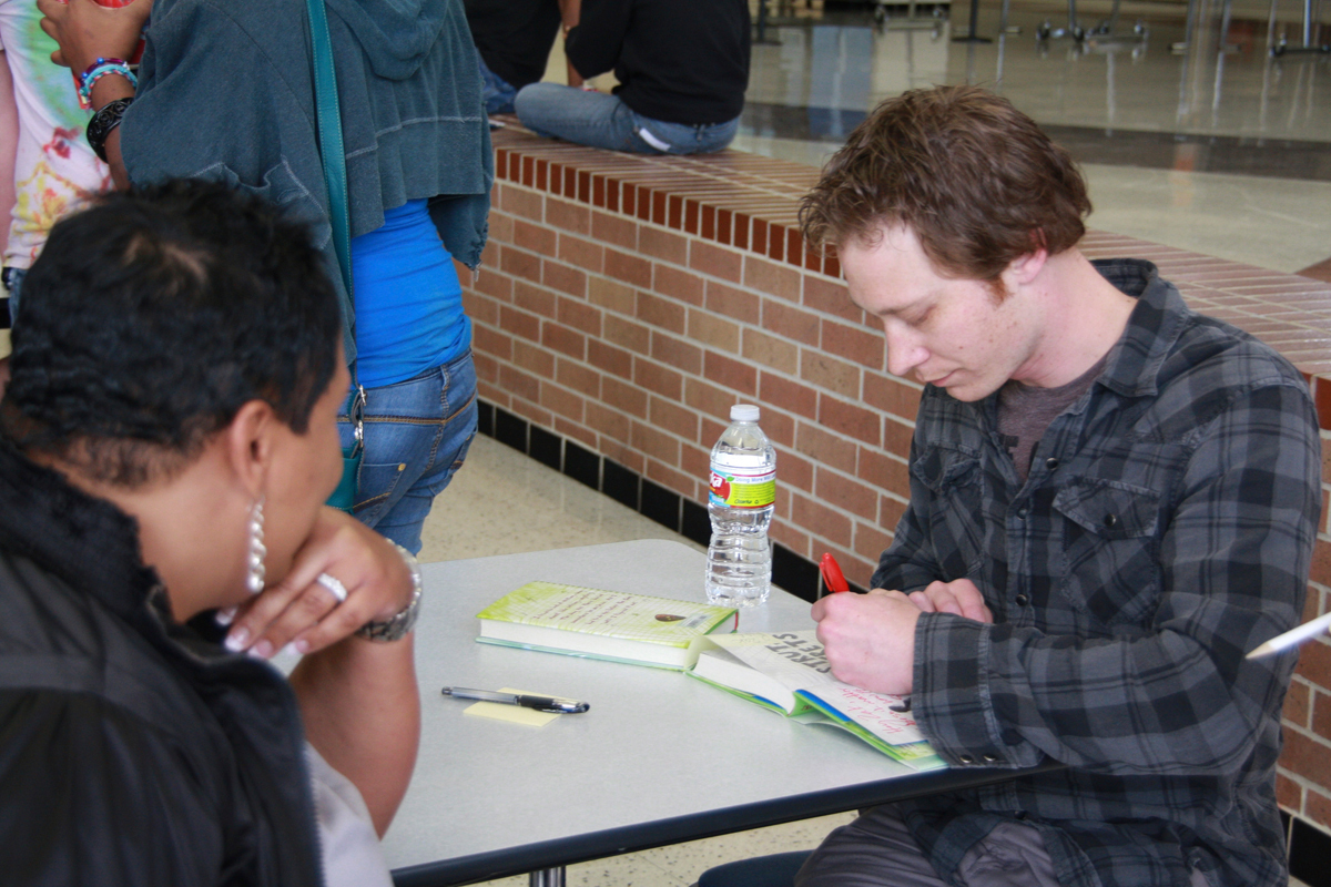 Author Jon Skovron autographs a copy of his first novel, _Struts and Frets_. (credit: Courtesy of libraryink via Flickr)