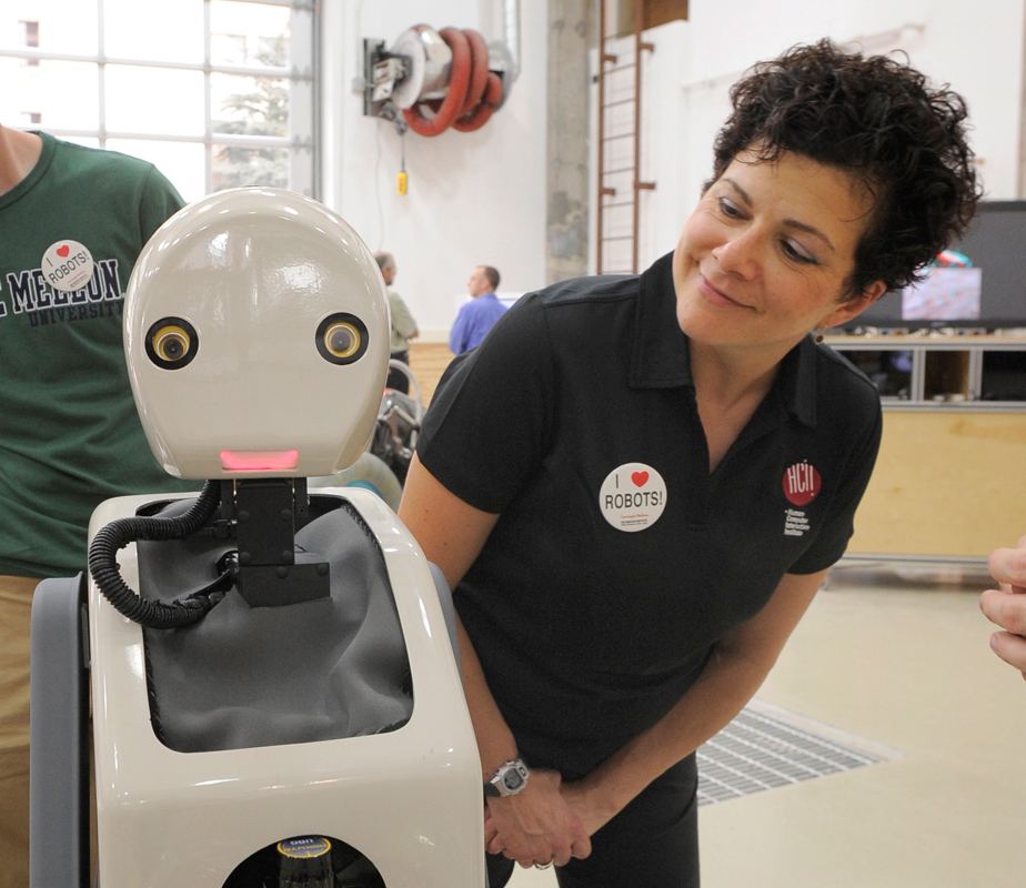"Jodi Forlizzi, a professor in the departments of design, human computer interaction, and computer science, poses with ""Snackbot,"" a snack-delivering robot aimed to help understand how people choose between different snacks. (credit: Photo courtesy of Jodi Forlizzi)"
