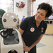 """Jodi Forlizzi, a professor in the departments of design, human computer interaction, and computer science, poses with """"Snackbot,"""" a snack-delivering robot aimed to help understand how people choose between different snacks."""