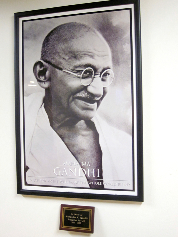 The OM spiritual group hung a plaque and portrait of Gandhi in the basement of the University Center last Wednesday. (credit: Jessica Sochol/)