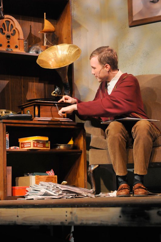The Man in Chair, played by sophomore computer  science major Matthew Alsup, plays the musical for the audience on his record player, occasionally  stopping the recording and freezing the action  onstage to offer his humorous commentary.    (credit: Courtesy of Guillermo Gomez)