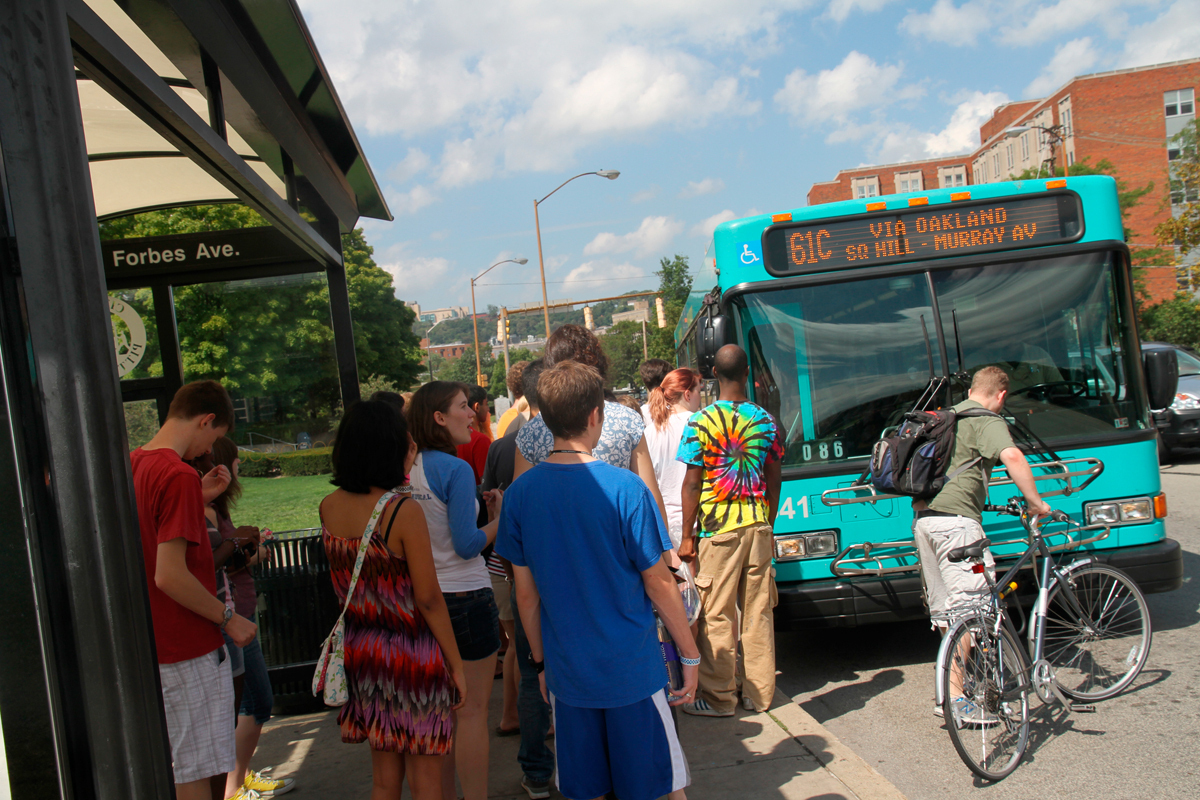 A crowd boards the 61C bus after a 25-minute wait. The 61C is one of many routes that would have had reduced service in September. (credit: Jonathan Carreon/Photo Editor)