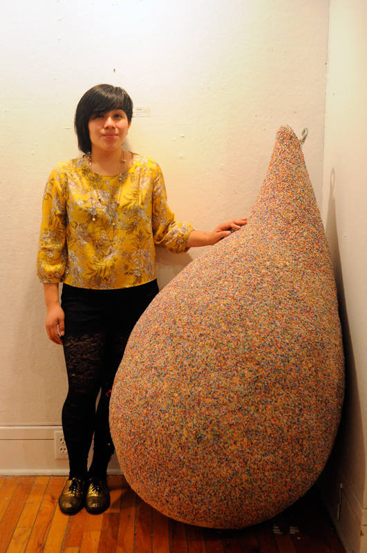 Senior art major Jessica Aguero stands next to one of her pieces at her Frame gallery opening last Friday. (credit: Alex Webster/)