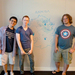 From left to right: Ben Chung, Josh Eiten, and Hank Zwally stand in front of the map of Annora, the fictional setting for their video game.