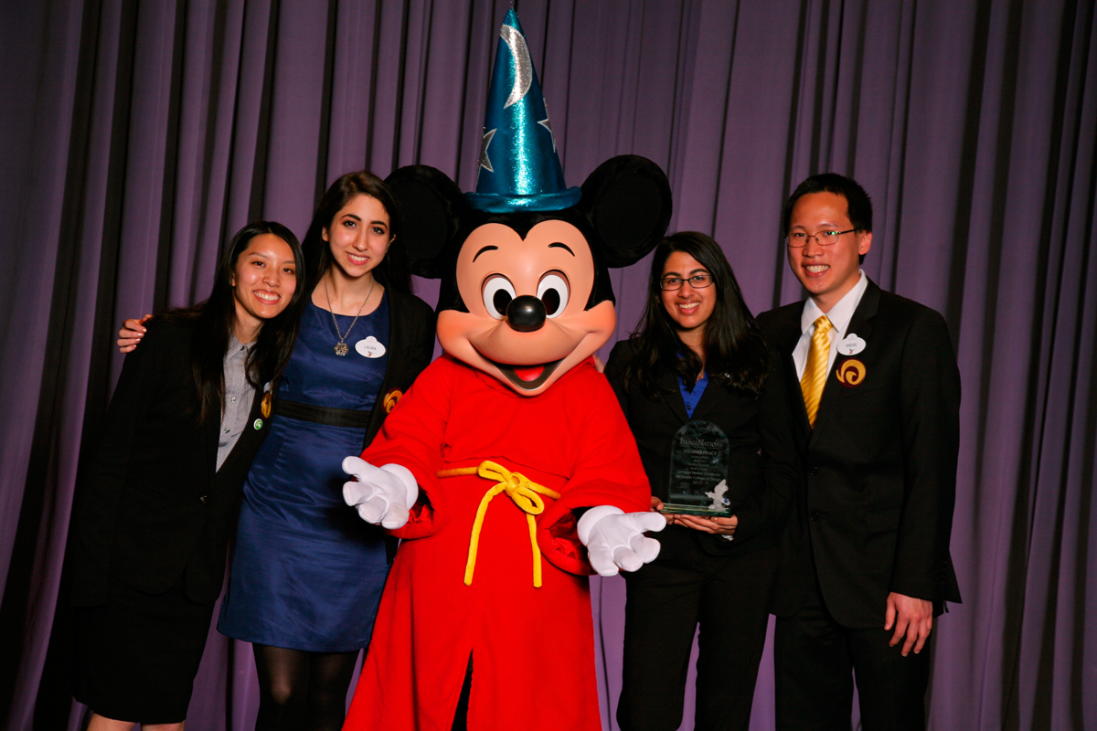 A team from Carnegie Mellon won second place in the 2013 ImagiNations Design Competition. Left to right is Jane Liu from Art Center College of Design, and Carnegie Mellon seniors Laura Laham, Anisha Vyas, and Andre Sutanto, posing with Mickey Mouse. (credit: © Disney. Photographer: Gary Krueger)
