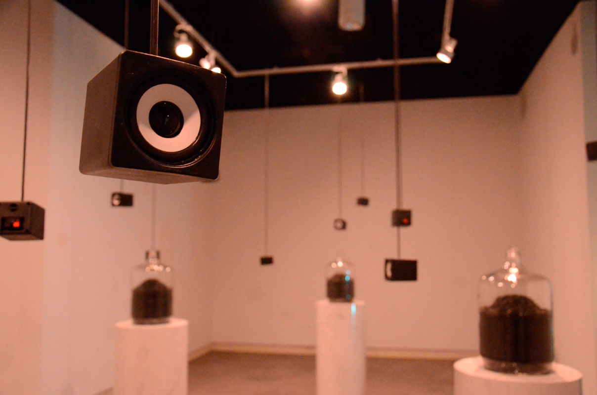 """""""Borderland"""" by Craig Fahner experiments with radio frequencies through an installation of hanging speakers and coal-filled jars. (credit: Kate Groschner/Photo Editor)"""