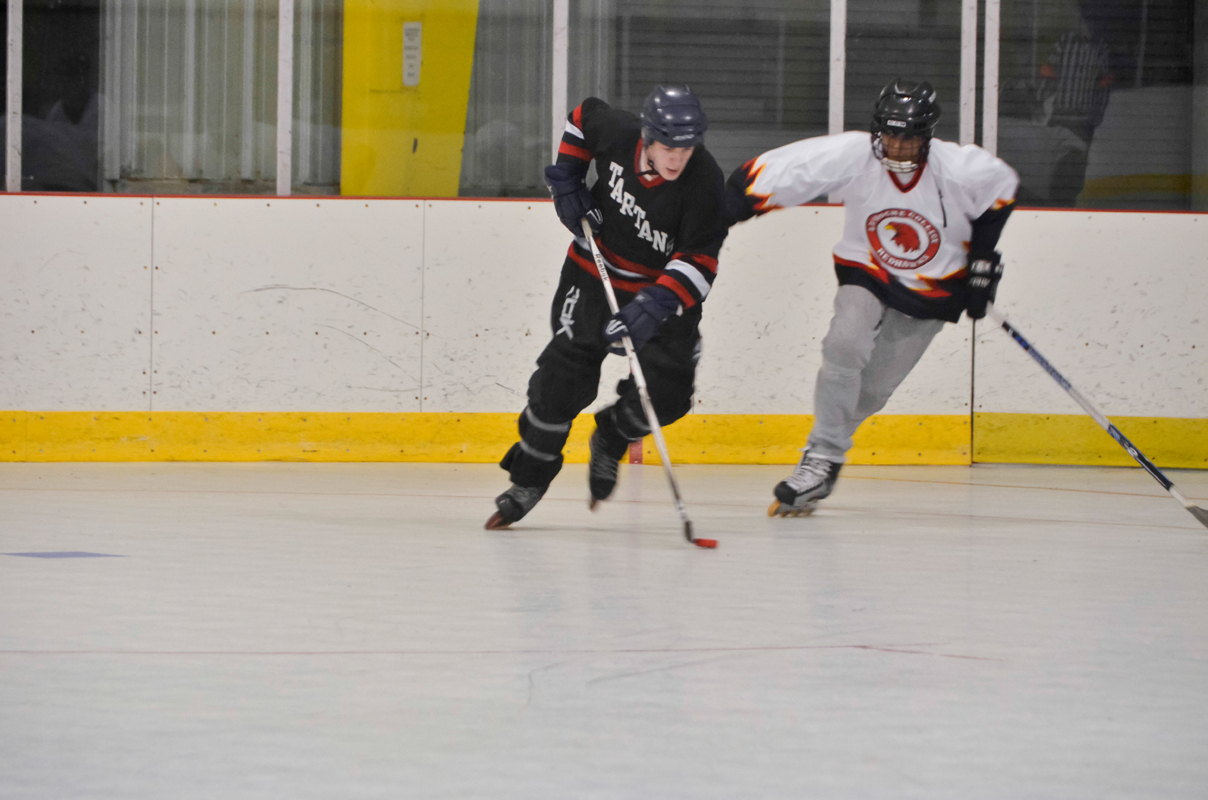 A Carnegie Mellon player maneuvers the puck away from a La Roche College defender during a game at the Island Sports Center. (credit: Courtesy of Daryl Hollinger)