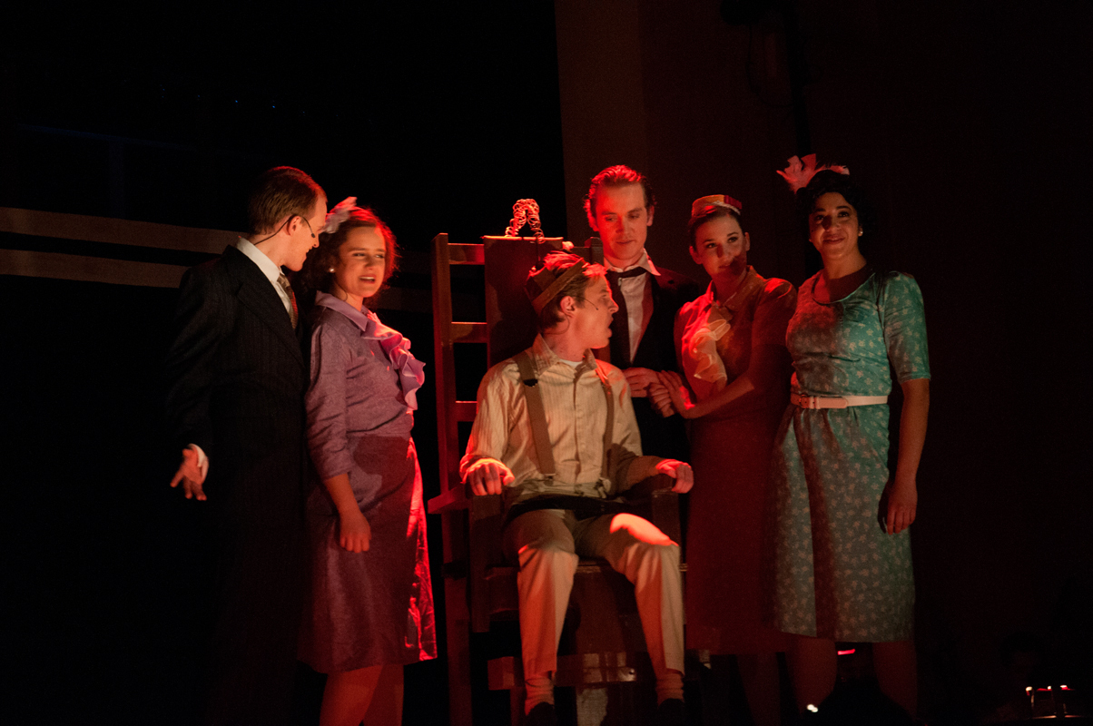 Members of the cast gather around Giuseppe Zangara, played by sophomore vocal performance major John Teresi, whose assassination attempt on President-elect Franklin D. Roosevelt was motivated by stomach pains. (credit: Kate Groschner/Photo Editor)
