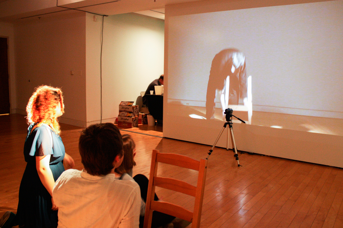 Attendees are given the chance to participate in the art in a portion of Yun Mi Her's segment of Lossless. Sitting in front of a camera, participants can see their image projected onto a screen on the other side of the gallery.   (credit: Maryyann Landlord/Comics Editor)