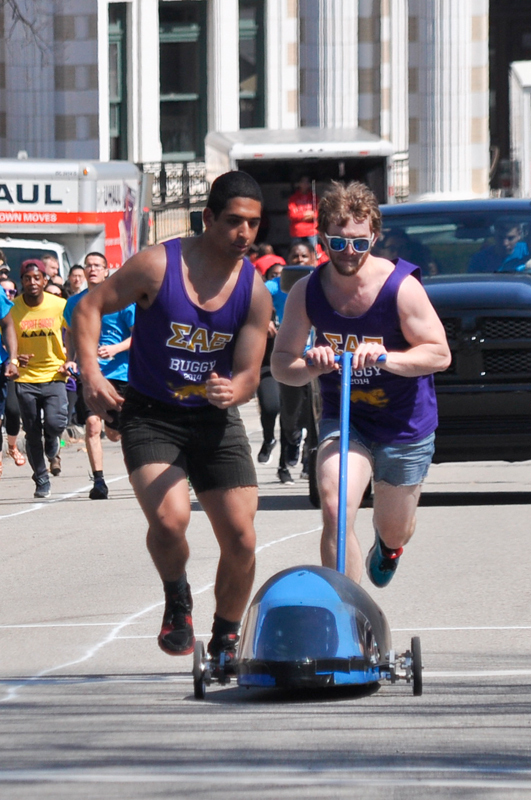 First-year Kerolos Mikaeil hands an SAE buggy off to junior Max Queenan. (credit: Alan Vangpat/Layout Staff)