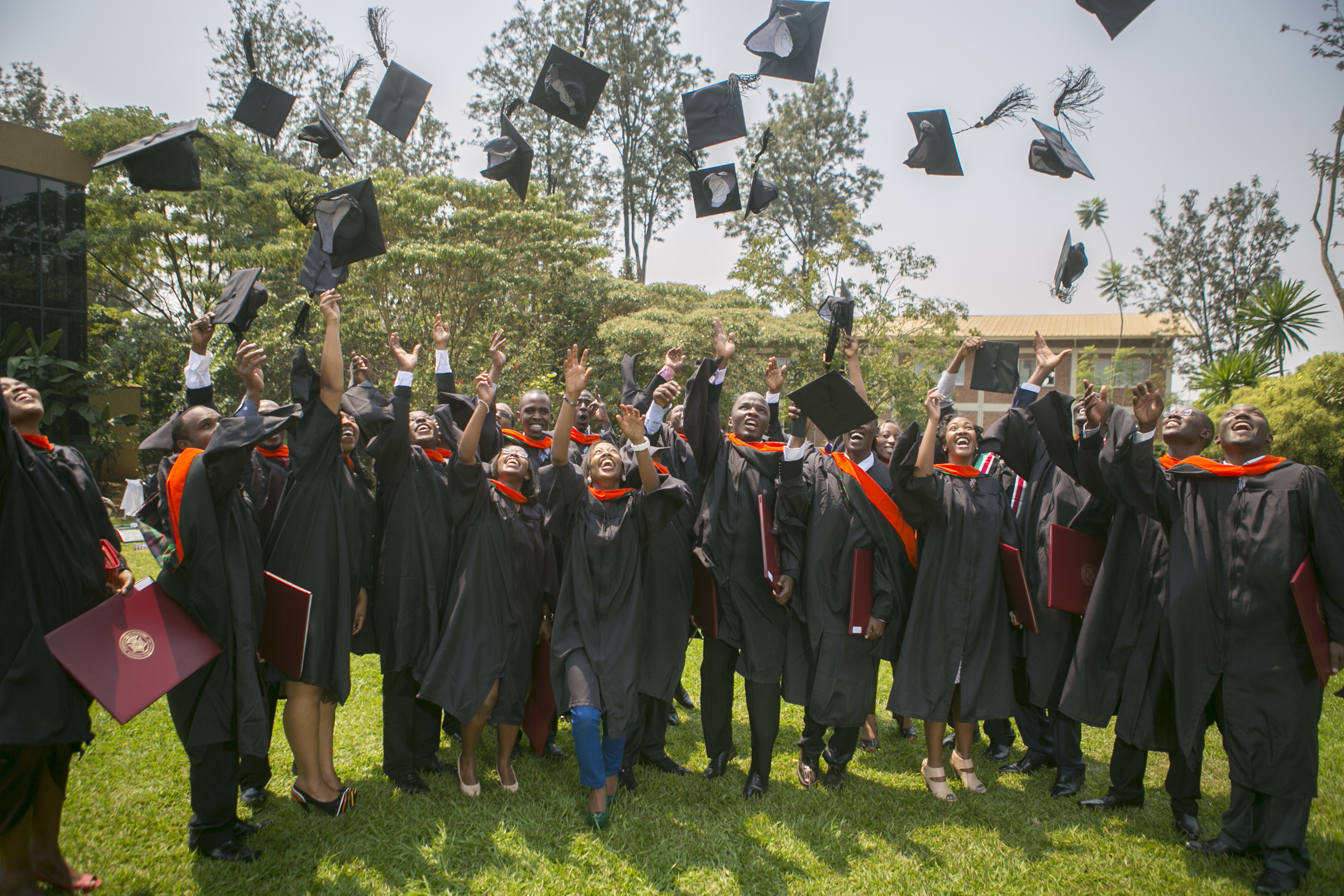New master's graduates toss their caps in the air at the inaugural graduation ceremony for Carnegie Mellon's Rwanda campus. 22 students received degrees in information technology on July 24. (credit: Courtesy of Philippe Nyirimihigo)