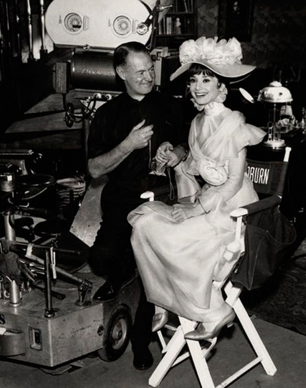 Audrey Hepburn, pictured here with cinematographer Harry Stradling, is largely credited with bringing My Fair Lady into American homes with her charming portrayal of Eliza Doolittle in the 1964 film.