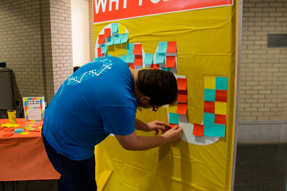A student writes why they volunteer on a Post-it note. (credit: Andy Birla/Staff Photographer)