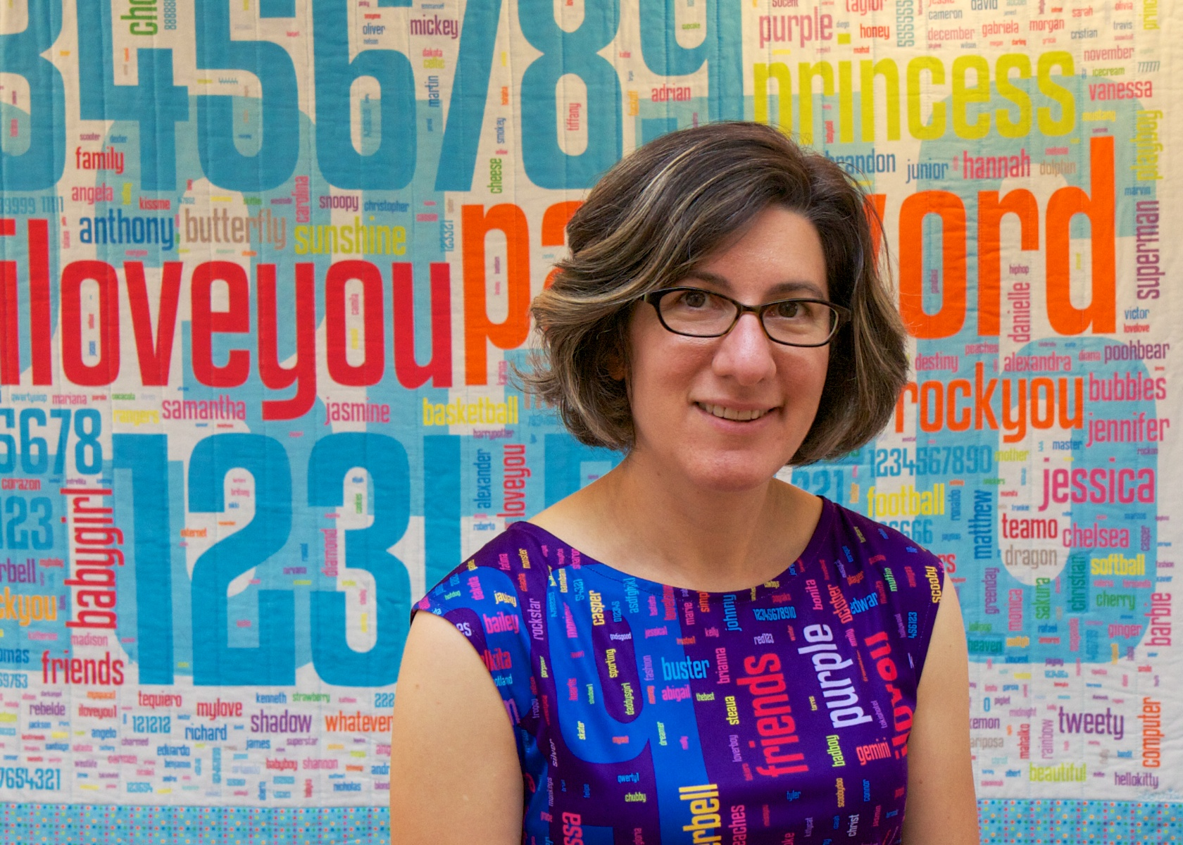 Lorrie Cranor stands in front of her quilt that depicts the frequencies of passwords in their respective sizes.