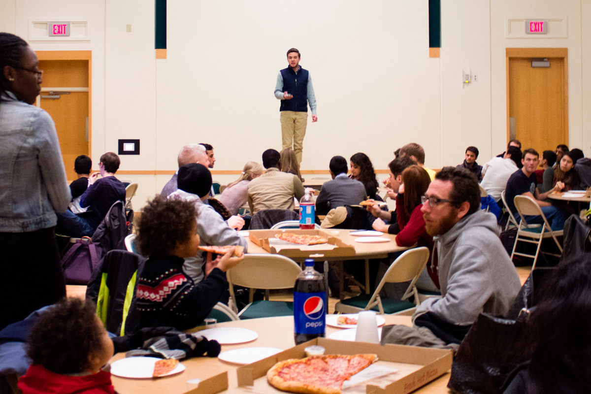 Evan Wineland, junior information systems major and Senate chair, welcomes students and faculty to Pizza + Politics, an event hosted by Senate to actively change the political apathy often found on CMU's campus. (credit: Kruti Koppolu/)