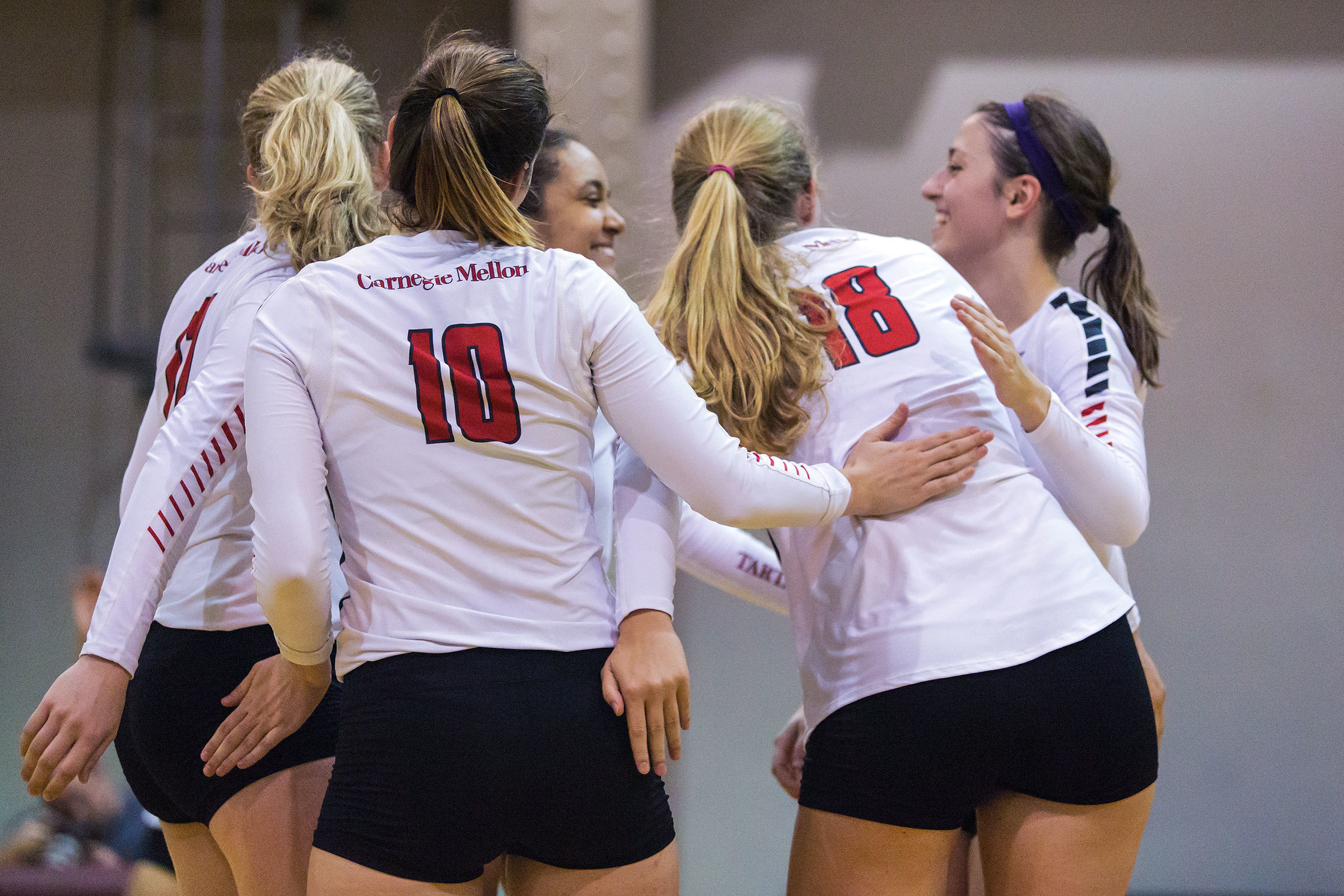 Sophomore outside hitter Hanna Wooten, first-year middle blocker Samantha Toomey, and others huddle. (credit: Junior Photographer)