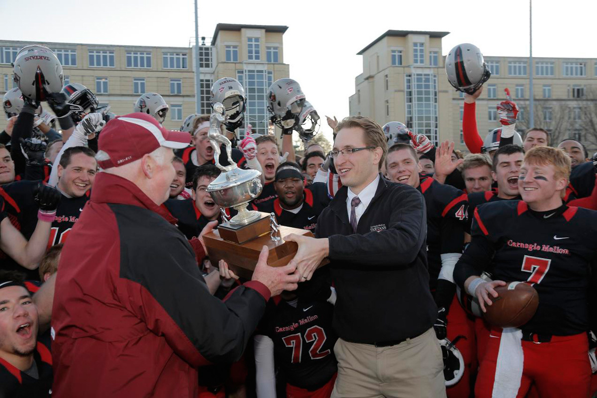 The Carnegie Mellon football team accepts the UAA championship trophy after earning a share of the conference championship. (credit: Courtesy of CMU Athletics)