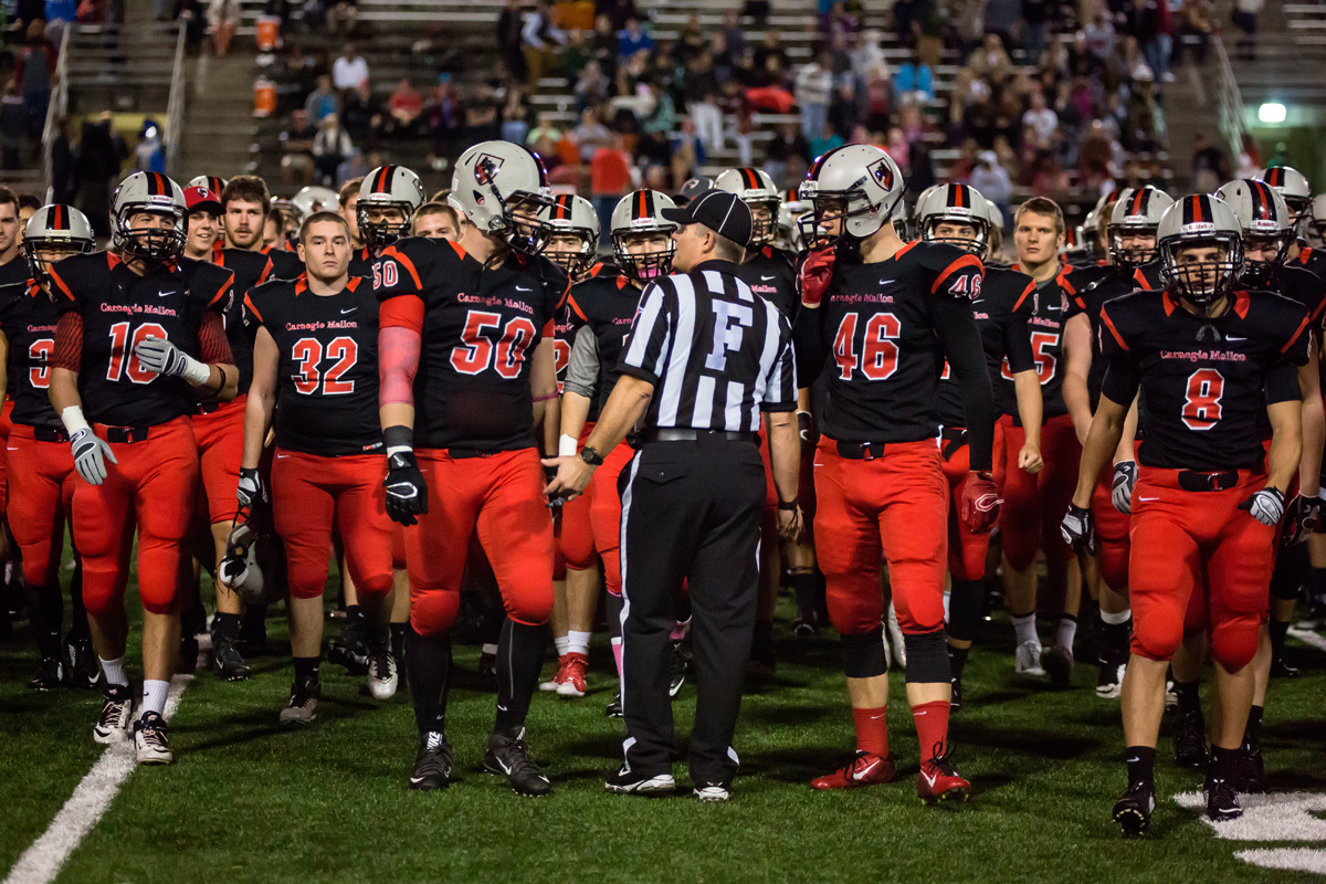The 2015 Carnegie Mellon football team huddles around a referee before the coin toss of a game in October.  (credit: File Photo Courtesy of Stefen Zhu)