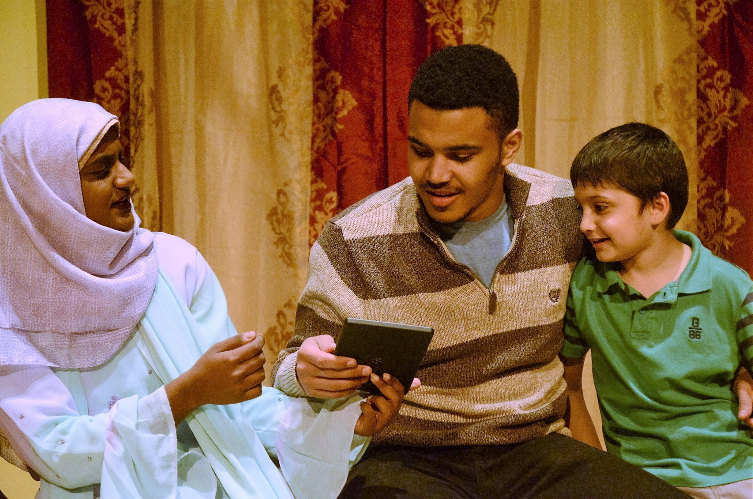 Akber (played by Hawkins) banters with Masuma (played by Mohamed) and her son Khali (played by Chickering). (credit: Theodore Teichman/Assistant Photo Editor)