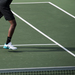 Senior Abhishek Alla extends to connect a backhand swing and returns a volley in the tennis match on Friday.