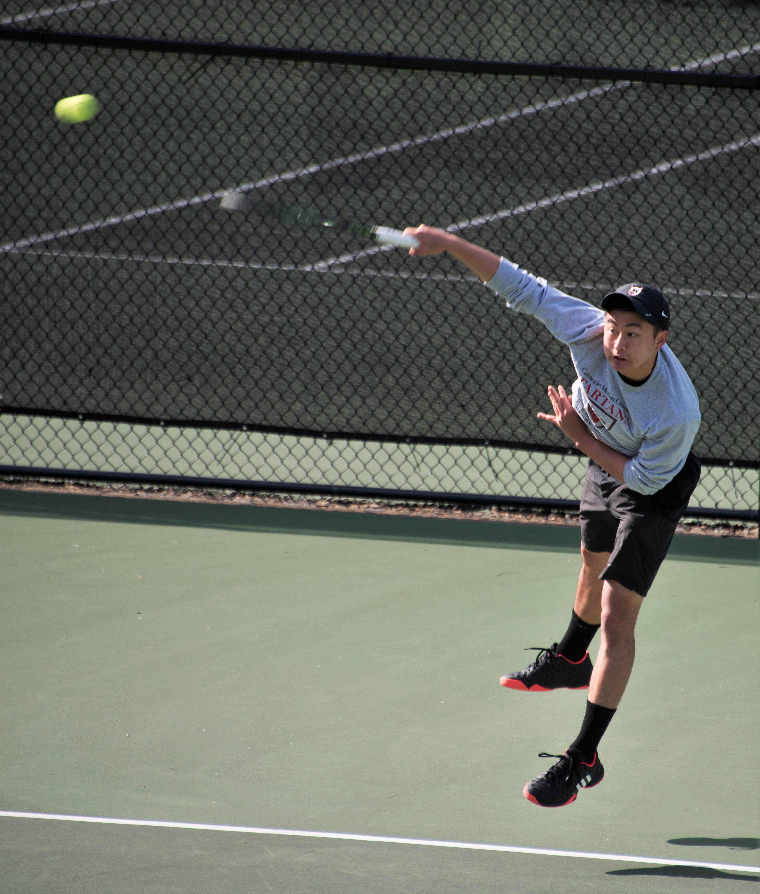 Junior Kenny Zheng leaps into the air to return a volley against Kenyon. (credit: Joshua Brown)