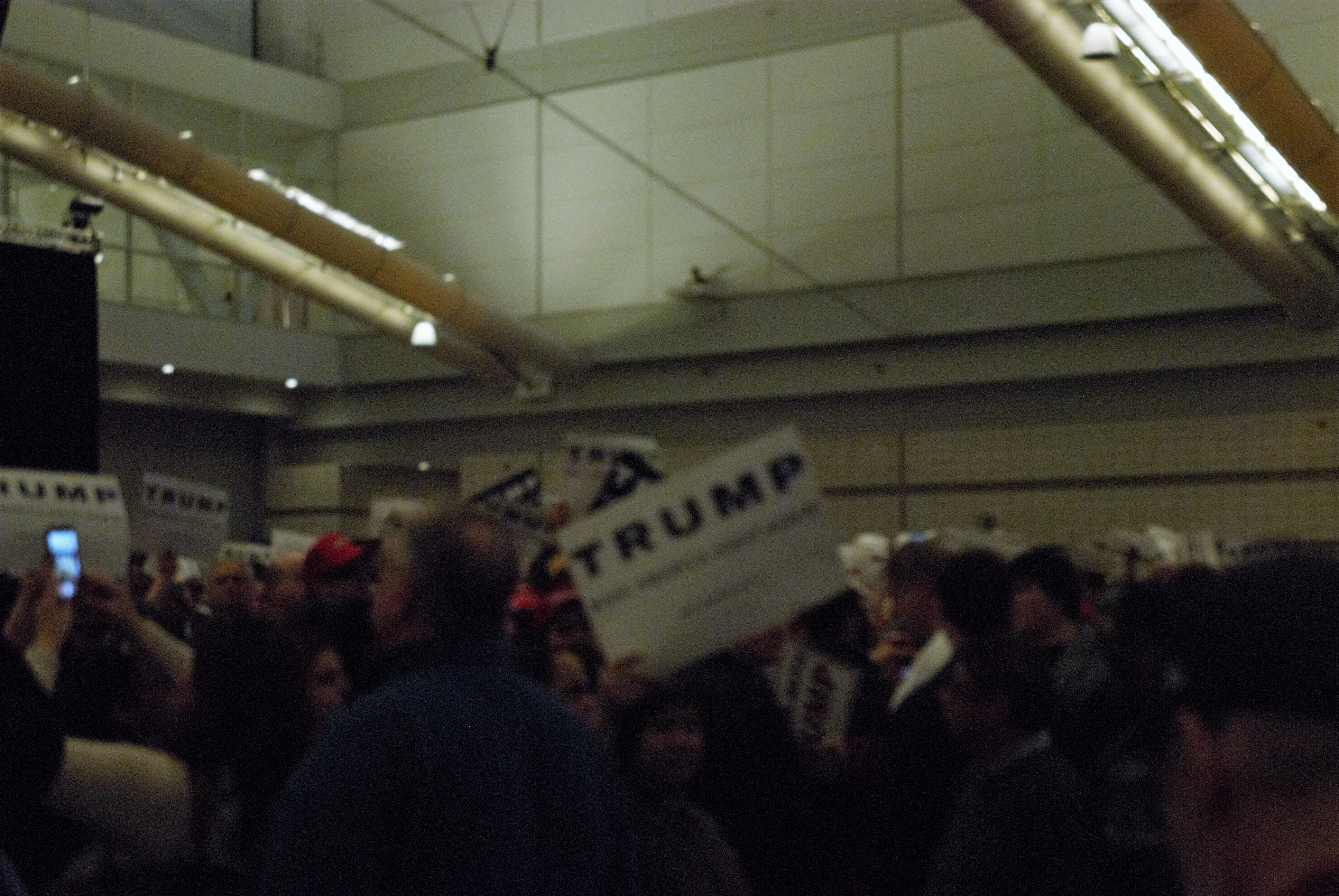 Trump supporters hold up signs in anticipation as 2 Unlimited blares through the loudspeakers indicating that Donald Trump is about to come out. Their phones are drawn in an attempt to catch a picture of Trump. (credit: Zeke Rosenberg/)