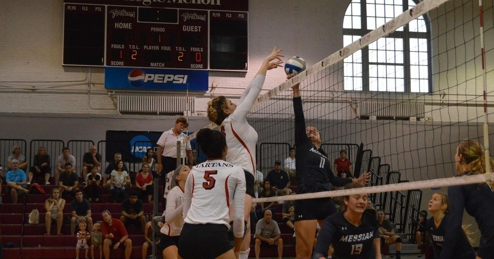 The volleyball team contests a play at the net as Messiah tries to tip the ball over the Tartans' wall of blockers. (credit: Courtesy of CMU Athletics)