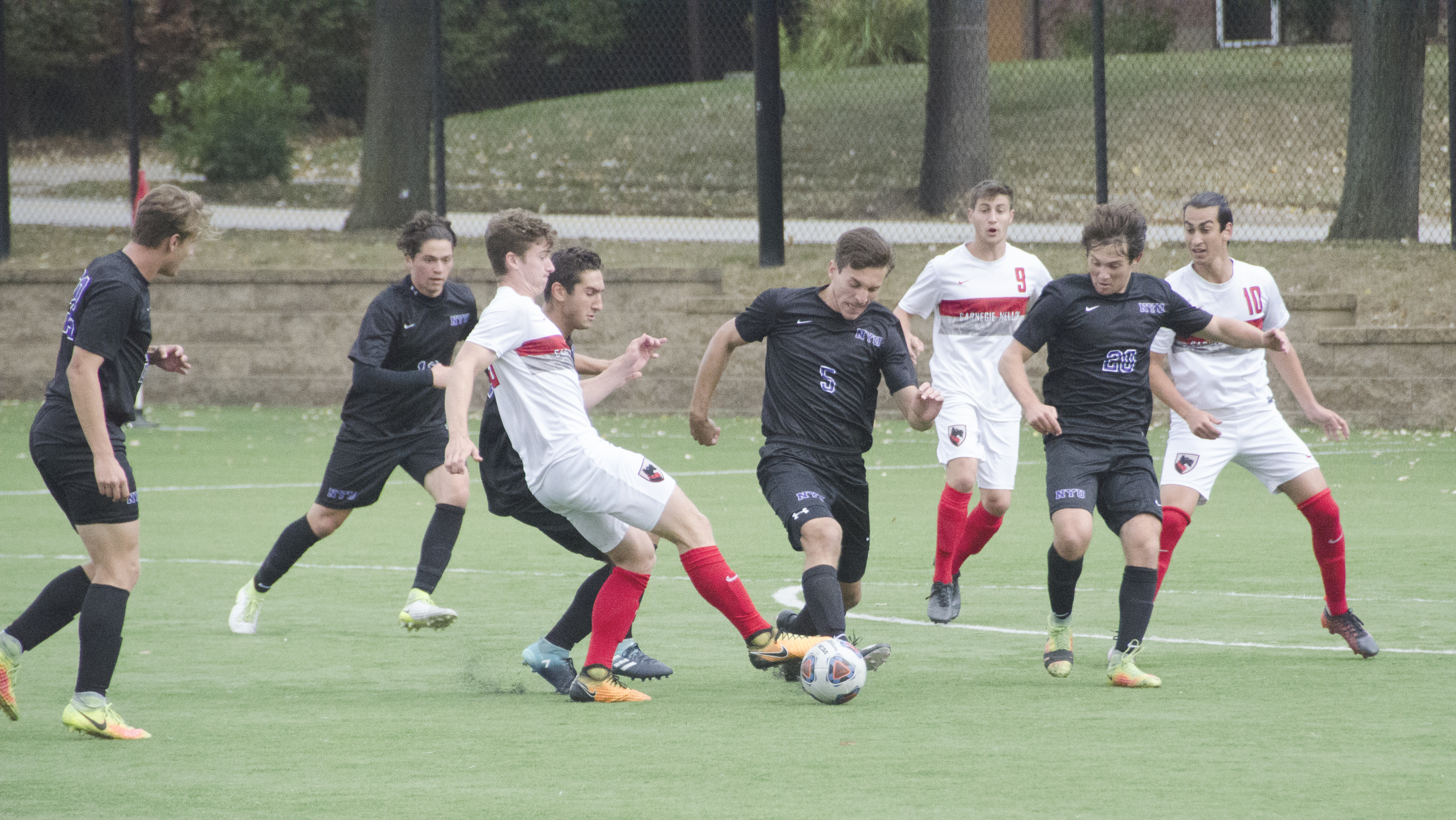The men's soccer team pressures New York University's defense, keeping the ball away from their side. (credit: Lisa Qian/ Staff Photographer)