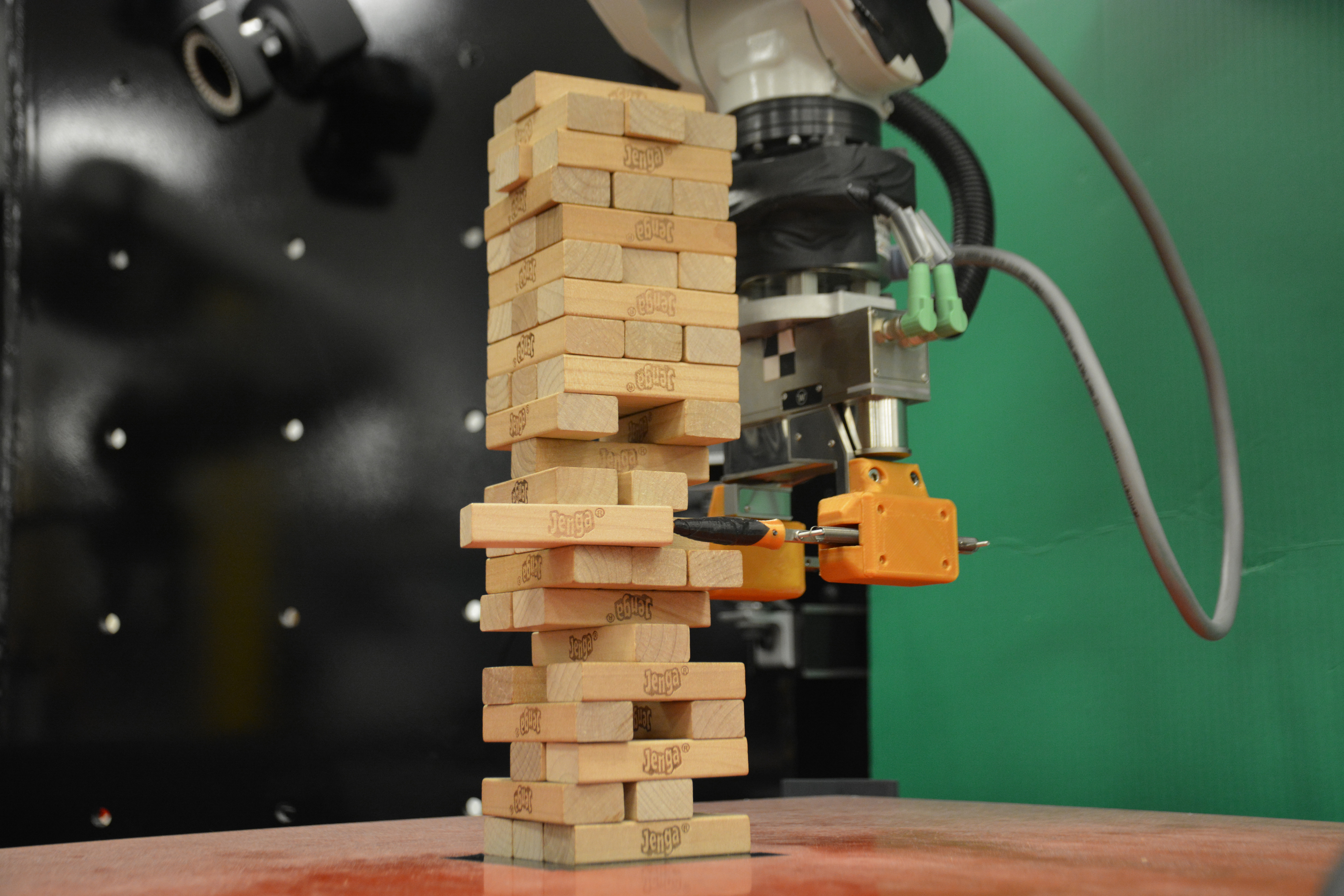 A robot designed by Carnegie Mellon alumnus Alberto Rodriguez and his team slowly pokes a wooden Jenga block out of a tower. Unlike traditional machine learning schemes, this robot takes careful visual and tactile measurements to model the behavior of Jenga blocks continuously, which has broad applications in manufacturing. (credit: Courtesy of the researchers via Massachusetts Institute of Technology)