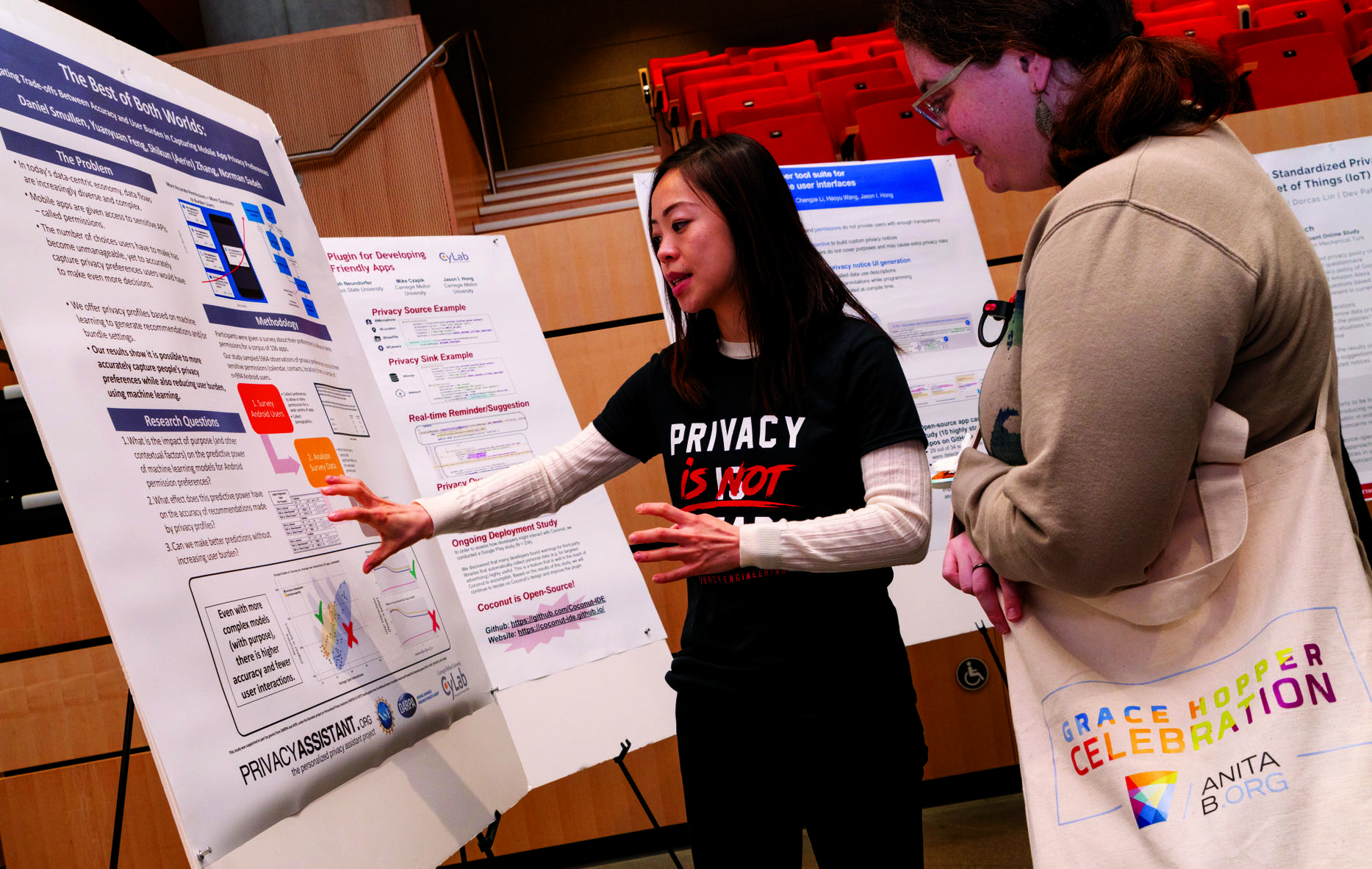 A researcher discusses her work on the privacyassistant.org project with an event attendee.