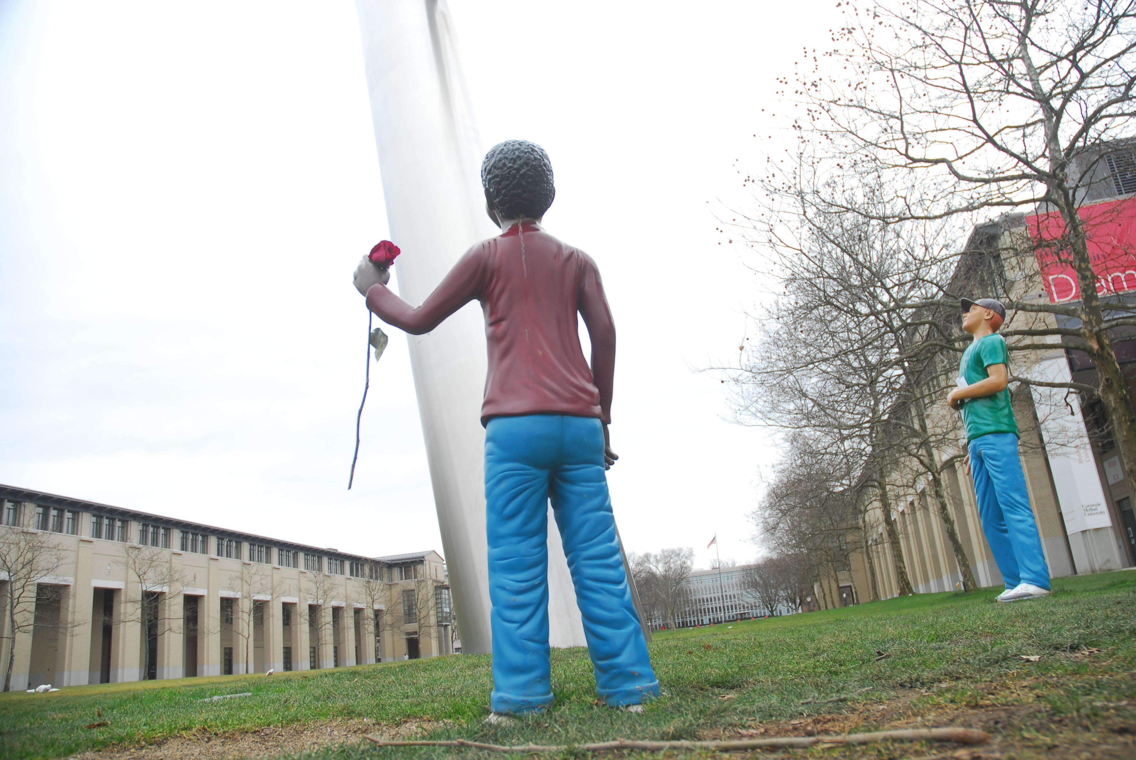 The young man who usually holds hands with *Walking to the Sky's* currently missing figure holds a rose, placed in his hand on Valentine's day. (credit: Adam Tunnard/News Editor)
